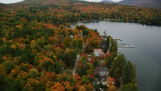 AX151_088 - 6K stock footage aerial video orbiting colorful forest, waterfront homes, Lake Sunapee, autumn, Newbury, New Hampshire