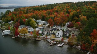 AX151_091 - 6K stock footage aerial video flying by waterfront homes, Lake Sunapee, autumn, Newbury, New Hampshire