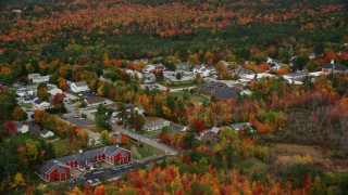 AX151_101 - 6K stock footage aerial video flying by Kearsarge Elementary School, small rural town, autumn, New London, New Hampshire