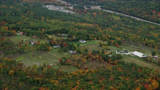 AX151_119 - 6K stock footage aerial video flying by rural homes, grassy clearings, colorful trees, autumn, Warner, New Hampshire