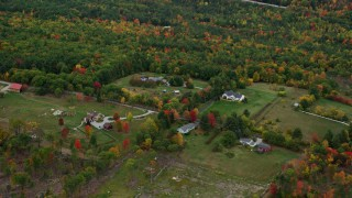 AX151_120 - 6K stock footage aerial video flying by rural homes, grassy clearings, colorful trees, autumn, Warner, New Hampshire