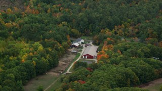 AX151_121 - 6K stock footage aerial video flying by barns, colorful trees in autumn, Warner, New Hampshire