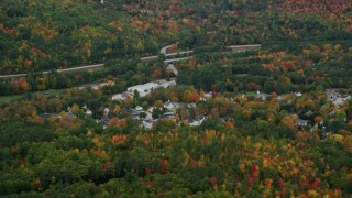 AX151_122 - 6K stock footage aerial video flying by small rural town, colorful foliage, autumn, Warner, New Hampshire