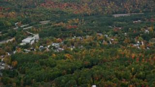 AX151_123 - 6K stock footage aerial video flying by small rural town, autumn trees, Warner, New Hampshire