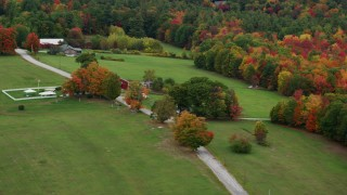 AX151_124 - 6K stock footage aerial video flying by grassy clearings, red barn, colorful trees, autumn, Warner, New Hampshire