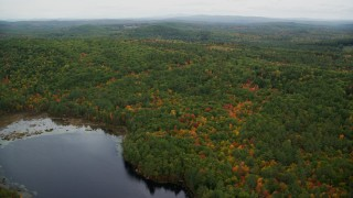 AX151_125 - 6K stock footage aerial video flying over Trumbull Pond, forest in autumn, overcast, Webster, New Hampshire