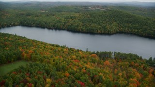 AX151_127 - 6K stock footage aerial video flying over Lake Winnepocket, dense forest, autumn, overcast, Webster, New Hampshire