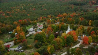 AX151_131 - 6K stock footage aerial video orbiting small rural town, Webster Congregational Church autumn, Webster, New Hampshire