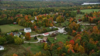 AX151_134 - 6K stock footage aerial video orbiting brightly colored foliage, a small rural town, church,  Webster, New Hampshire