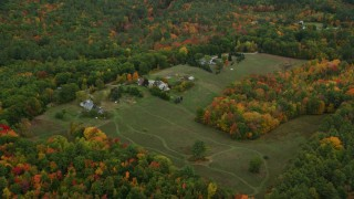 AX151_140 - 6K stock footage aerial video approaching rural homes, grassy clearing, tilt down, autumn, Penacook, New Hampshire