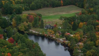 AX151_141 - 6K stock footage aerial video flying by waterfront homes, Contoocook River, autumn, Penacook, New Hampshire