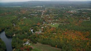 AX151_142 - 6K stock footage aerial video approaching small rural town, river, trees, autumn, Penacook, New Hampshire
