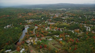 AX151_143 - 6K stock footage aerial video approaching small town neighborhood near river, autumn, Penacook, New Hampshire