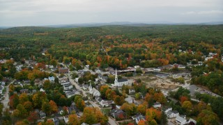 AX151_146 - 6K stock footage aerial video orbiting small town neighborhood, churches, autumn, overcast, Penacook, New Hampshire