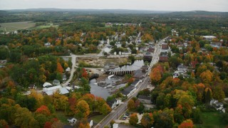 AX151_148 - 6K stock footage aerial video orbiting Main Street, small town, Contoocook River, autumn, Penacook, New Hampshire
