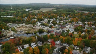 AX151_149 - 6K stock footage aerial video orbiting small town, church, dam, Contoocook River, autumn, Penacook, New Hampshire