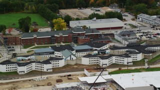 AX151_172 - 6K stock footage aerial video flying by the New Hampshire State Prison in autumn, Concord, New Hampshire