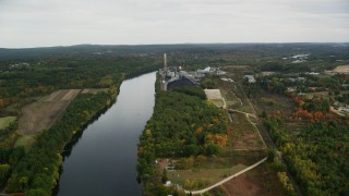 AX152_004 - 6K stock footage aerial video flying over Merrimack River, approaching a power plant, autumn, Bow, New Hampshire