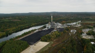 AX152_005 - 6K stock footage aerial video flying by Merrimack River, approaching a power plant, autumn, Bow, New Hampshire