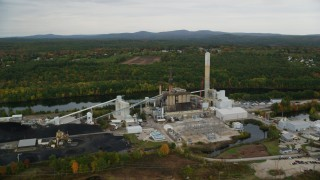 AX152_006 - 6K stock footage aerial video flying by a power plant, colorful foliage in autumn, Bow, New Hampshire