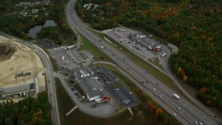 AX152_008 - 6K stock footage aerial video approaching strip malls, Interstate 93, tilt down, autumn, Bow, New Hampshire