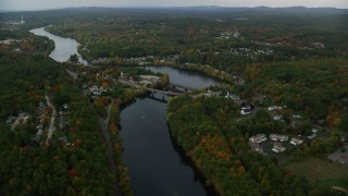 AX152_012 - 6K stock footage aerial video orbiting small bridges, Merrimack River, small town, autumn, Hooksett, New Hampshire