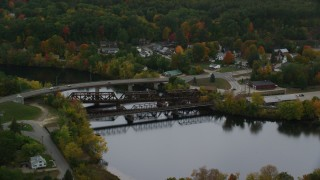 AX152_014 - 6K stock footage aerial video orbiting small bridges, Merrimack River, autumn, Hooksett, New Hampshire