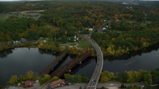 AX152_017 - 6K stock footage aerial video flying over Merrimack River, College Park Road through small town, autumn, Hooksett, New Hampshire