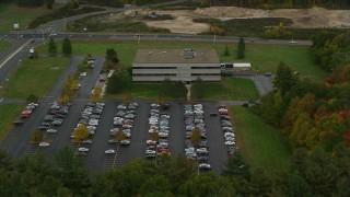 AX152_018 - 6K stock footage aerial video approaching an office building, tilt down, autumn, Hooksett, New Hampshire