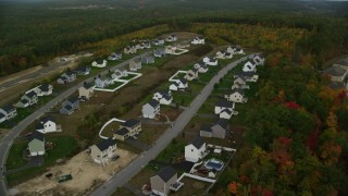 AX152_020 - 6K stock footage aerial video flying by tract homes, colorful foliage in autumn, Hooksett, New Hampshire