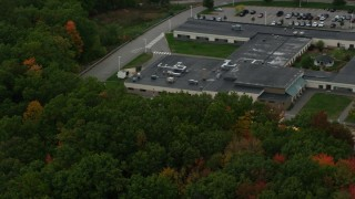 AX152_025 - 6K stock footage aerial video flying by Hooksett Memorial School, colorful foliage, autumn, Hooksett, New Hampshire