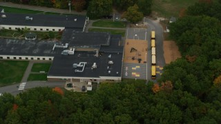 AX152_026 - 6K stock footage aerial video orbiting Hooksett Memorial School, revealing buses, autumn, Hooksett, New Hampshire