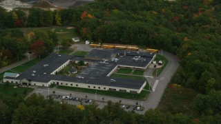 AX152_027 - 6K stock footage aerial video orbiting Hooksett Memorial School, buses, autumn, Hooksett, New Hampshire