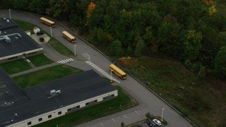AX152_028 - 6K stock footage aerial video orbiting Hooksett Memorial School, tracking buses leaving, autumn, Hooksett, New Hampshire