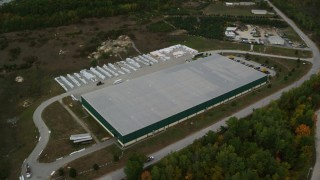 AX152_030 - 6K stock footage aerial video flying by warehouse building, colorful foliage, autumn, Hooksett, New Hampshire