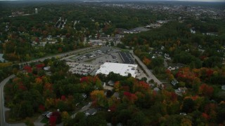 AX152_035 - 6K stock footage aerial video flying over colorful foliage, approaching a store, tilt down, autumn, Manchester, New Hampshire