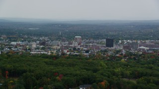 AX152_042 - 6K stock footage aerial video flying by downtown office towers, overcast skies, autumn, Manchester, New Hampshire