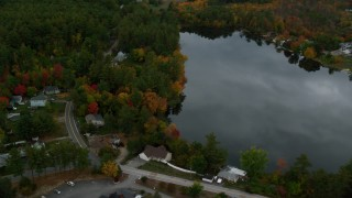 AX152_049 - 6K stock footage aerial video flying by Crystal Lake, waterfront homes, autumn, Manchester, New Hampshire