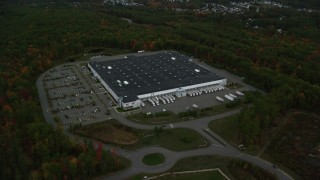 AX152_052 - 6K stock footage aerial video flying away from a warehouse building, dense forest, autumn, Londonderry, New Hampshire