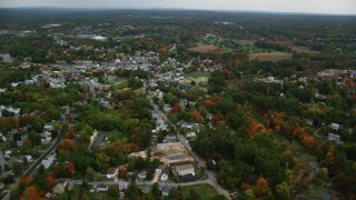 AX152_056 - 6K stock footage aerial video flying by homes, downtown area, colorful foliage in autumn, Derry, New Hampshire