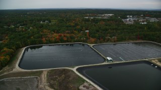 AX152_062 - 6K stock footage aerial video flying by water treatment plant ponds, colorful foliage, autumn, Derry, New Hampshire