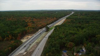 AX152_064 - 6K stock footage aerial video flying over Interstate 93 through colorful foliage in autumn, Derry, New Hampshire