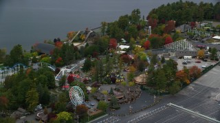 AX152_072 - 6K stock footage aerial video orbiting Canobie Lake Park, colorful trees in autumn, Salem, New Hampshire