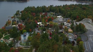 AX152_073 - Aerial stock footage of 6K aeria video orbiting colorful foliage, Canobie Lake Park, autumn, Salem, New Hampshire