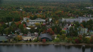 AX152_075 - 6K stock footage aerial video orbiting trees, waterfront Canobie Lake Park, autumn, Salem, New Hampshire