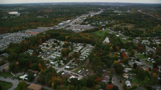 AX152_082 - 6K stock footage aerial video flying by mobile home park, stores, autumn, Salem, New Hampshire