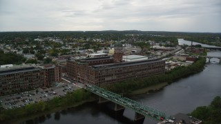 AX152_102 - 6K stock footage aerial video of a factory and clock tower by the water, overcast, Lawrence, Massachusetts