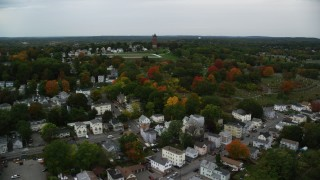 AX152_113 - 6K stock footage aerial video flying over fall trees toward a cemetery and water tower, autumn, Lawrence, Massachusetts