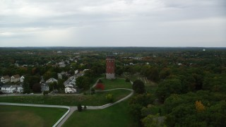 AX152_114 - 6K stock footage aerial video approaching a water tower and trees with fall color, autumn, Lawrence, Massachusetts