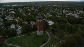 AX152_115 - 6K stock footage aerial video orbiting away from a water tower and town with fall trees, autumn, Lawrence, Massachusetts